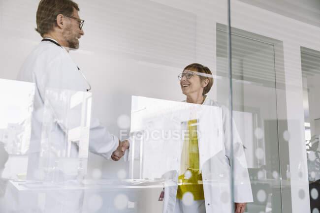 Zwei lächelnde Ärzte beim Händeschütteln hinter Glaswand — Stockfoto