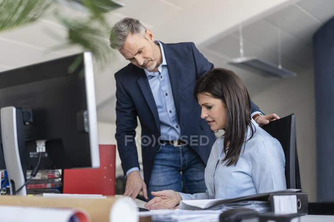 Geschäftsmann und Geschäftsfrau im Gespräch am Schreibtisch im Büro — Stockfoto