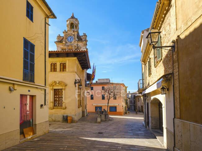 España, Islas Baleares, Mallorca, Alcudia, Calle del casco antiguo con torre de ayuntamiento en segundo plano - foto de stock