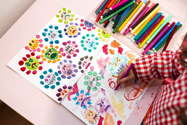 Niña dibujando virus feos con marcadores de color en casa - foto de stock