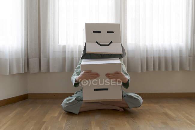 Mujer usando una caja de cartón en la cabeza con la cara sonriente, y cerrando los ojos de la caja de cartón sonriente aburrida - foto de stock