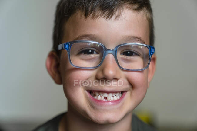 Portrait of little boy with tooth gap wearing blue glasses — Stock Photo
