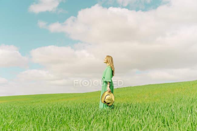 Blonde junge Frau in grünem Kleid steht auf einem Feld — Stockfoto