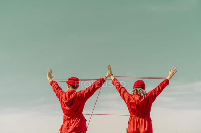 Vista posterior de la joven pareja con monos rojos y sombreros actuando con hilo rojo al aire libre - foto de stock