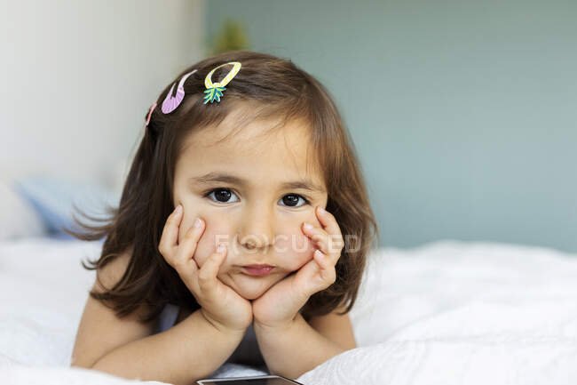 Portrait of bored little girl lying on bed — Stock Photo