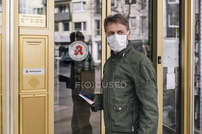 Homem com máscara esperando na frente da farmácia segurando prescrição — Fotografia de Stock