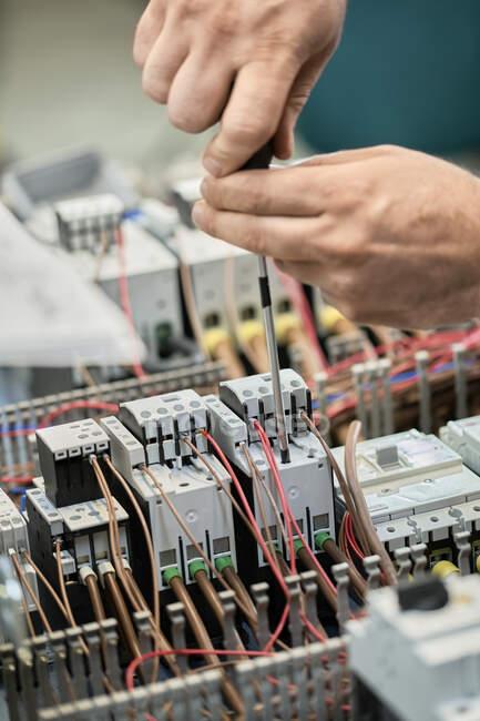 Nahaufnahme eines Elektrikers, der an Schaltkreisen arbeitet — Stockfoto