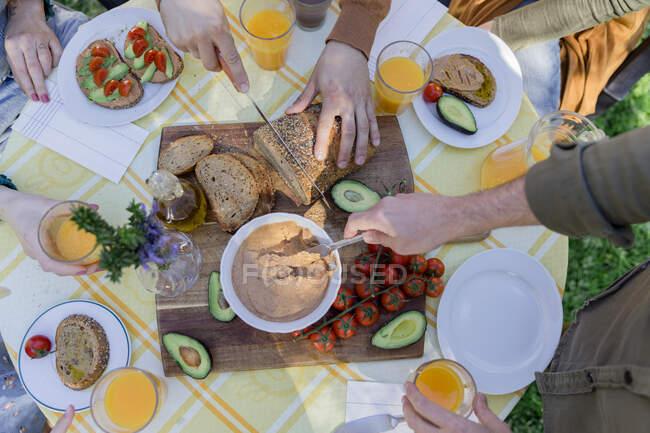 Close-up of friends enjoying a healthy vegan breakfast outdoors — Stock Photo