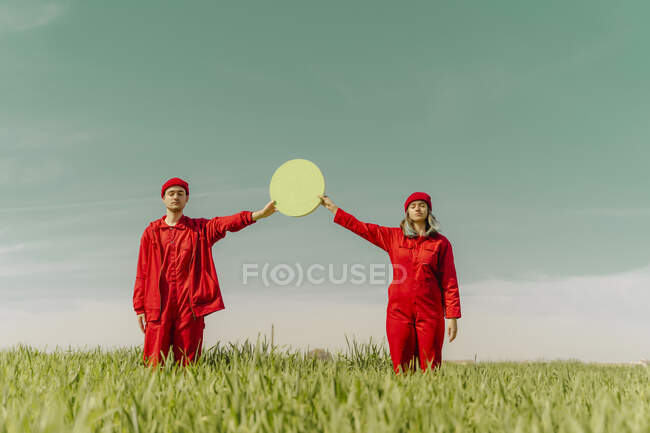 Pareja joven vestida con monos rojos de pie en un campo con círculo verde - foto de stock