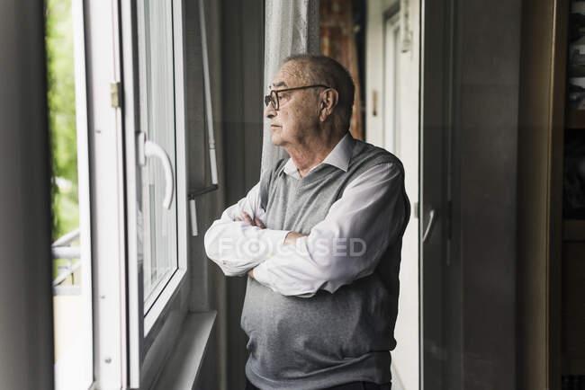 Homem idoso pensativo olhando pela janela — Fotografia de Stock