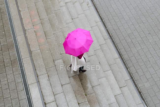 Mujer con paraguas rosa en las escaleras - foto de stock
