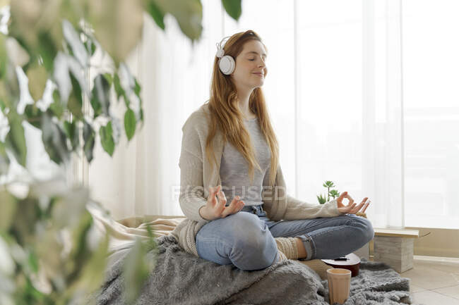 Young woman wearing headphones and practicing yoga at home — стокове фото