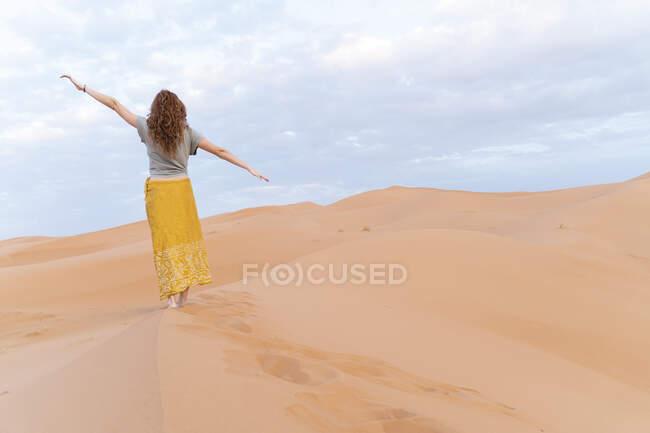 Giovane donna in piedi su una duna di sabbia nel deserto del Sahara con le braccia tese, Merzouga, Marocco — Foto stock