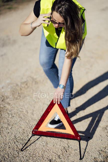 Mujer con una ruptura posteando triángulo de advertencia - foto de stock