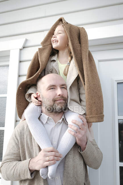 Portrait of father with happy daughter on his shoulders in front of their house — Stock Photo