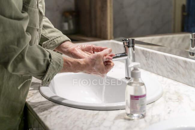 Hombre lavándose las manos con desinfectante - foto de stock