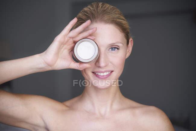Портрет улыбающейся красивой женщины, держащей банку крема перед глазами — стоковое фото