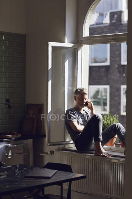 Hombre maduro sentado en la ventana en casa hablando por teléfono - foto de stock