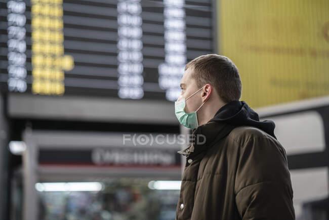 Молодий чоловік з маскою обличчя на залізничному вокзалі в місті. — стокове фото