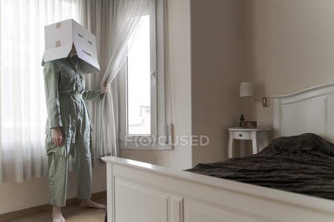 Mulher vestindo uma caixa de papelão na cabeça com um sorriso entediado olhando pela janela — Fotografia de Stock