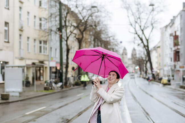 Mujer sonriente con paraguas rosa caminando por la calle — Stock Photo