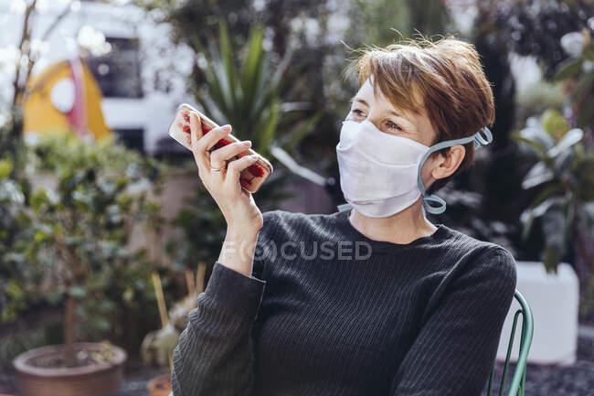 Mulher com máscara facial sentada no jardim, falando ao telefone — Fotografia de Stock