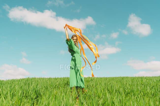 Feliz joven con un vestido verde en un campo con cintas que soplan - foto de stock