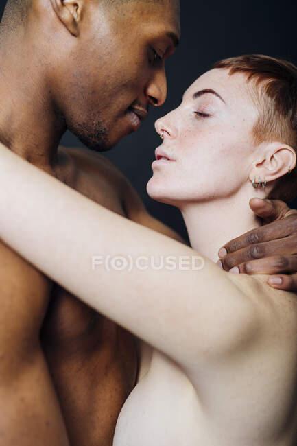 Estúdio retrato de afetuoso nu mestiço casal abraço — Fotografia de Stock