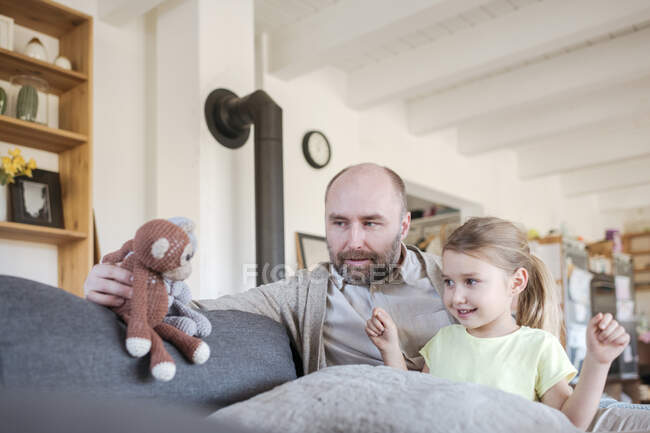 Father and little daughter sitting together on the couch at home playing with toys — Stock Photo