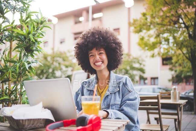 Jovem feliz com penteado afro usando laptop em um café ao ar livre na cidade — Fotografia de Stock