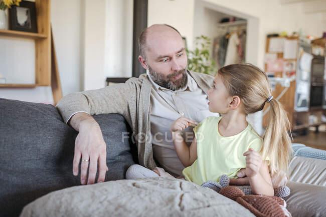 Батько з донькою сидять разом на дивані і веселяться. — стокове фото