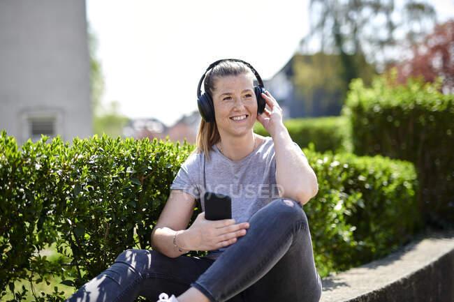 Улыбающаяся женщина смотрит в сторону, слушая музыку через наушники на смартфоне растений — стоковое фото