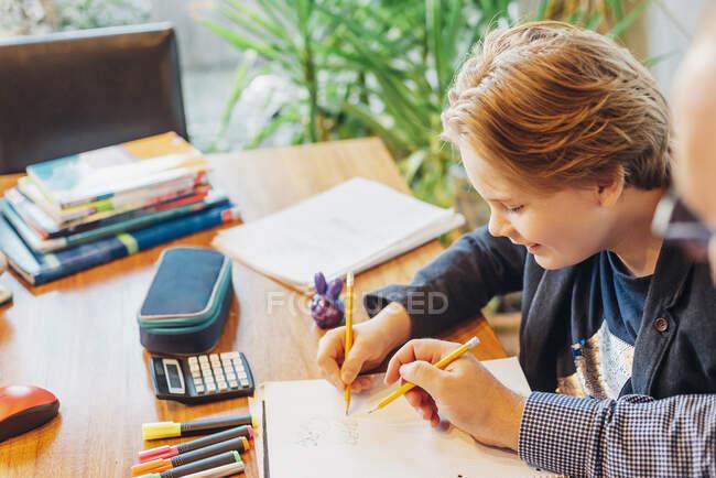 Père aidant son fils à faire ses devoirs au bureau — Photo de stock