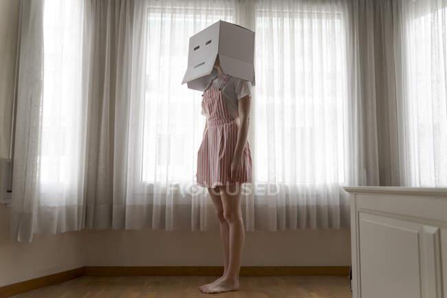 Mujer con una caja de cartón en la cabeza con sonrisa aburrida mirando por la ventana en casa - foto de stock