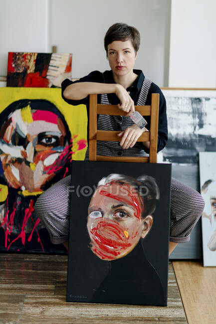 Portrait of a female painter sitting on a chair in her studio — Stock Photo
