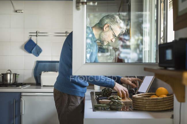 Hombre maduro preparando alcachofa en su cocina usando tableta digital - foto de stock