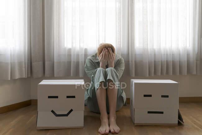 Mujer sentada entre diferentes cajas de cartón en casa, sonriente y aburrida caja de cartón - foto de stock