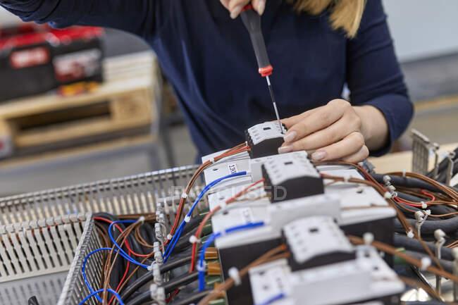 Nahaufnahme eines Elektrikers, der in der Werkstatt an Schaltkreisen arbeitet — Stockfoto
