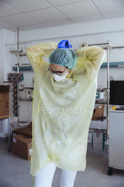 Médico decolando equipamentos de proteção individual no hospital — Fotografia de Stock