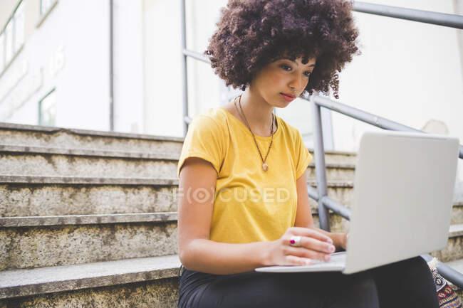 Jeune femme avec une coiffure afro en utilisant un ordinateur portable dans les escaliers de la ville — Photo de stock