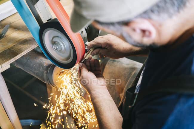 Handwerker, der in seiner Werkstatt Messer herstellt, schärft die Klinge — Stockfoto