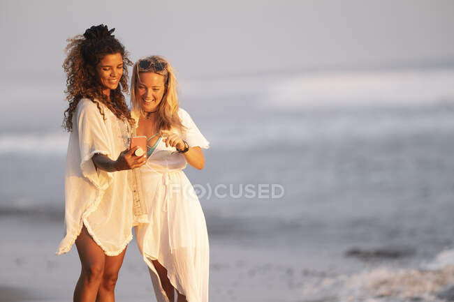 Dos mujeres felices en la playa usando smartphone, Costa Rica - foto de stock