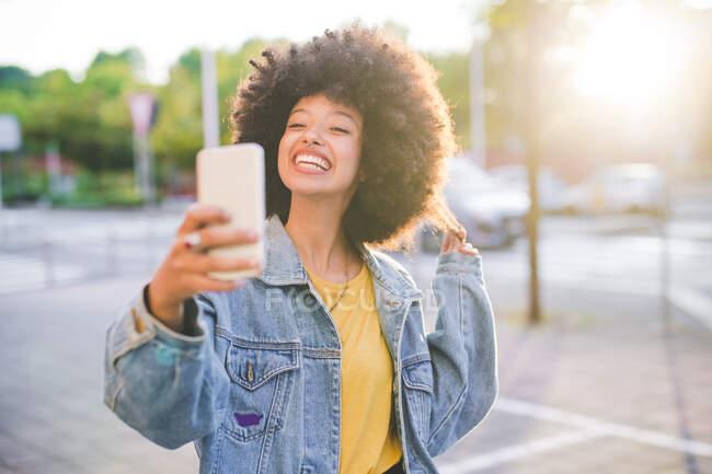 Felice giovane donna con acconciatura afro prendendo un selfie in città — Foto stock