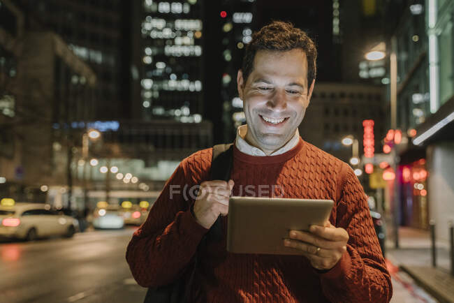 Portrait of happy entrepeneur in the city looking at digital tablet at night, Frankfurt, Germany — Stock Photo