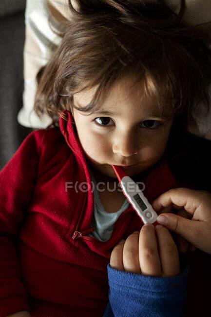 Retrato de niña enferma tumbada en el sofá con termómetro digital, manos de madre - foto de stock