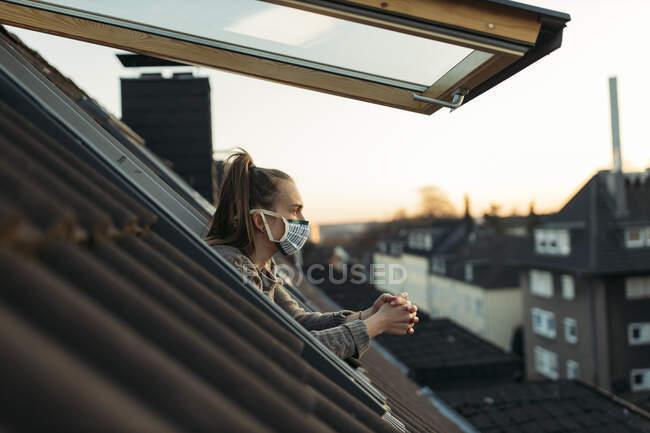 Молодая женщина в маске смотрит в окно — стоковое фото