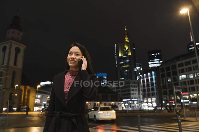 Молода жінка вночі телефоном у місті Франкфурт (Німеччина). — стокове фото
