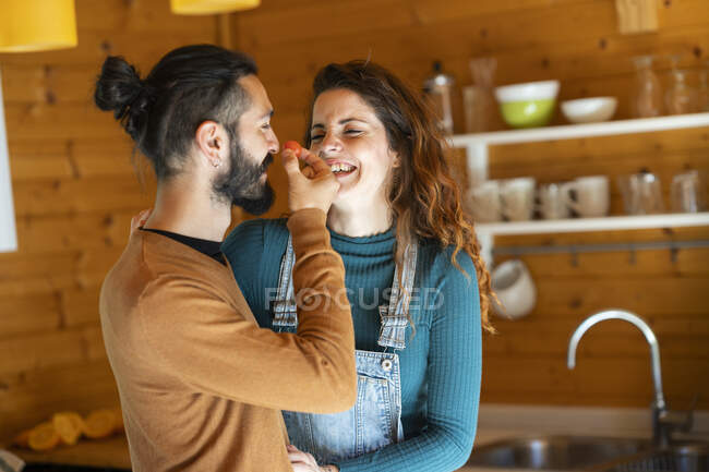 Happy young couple playing with a cherry tomato in a wooden cabin — Stock Photo