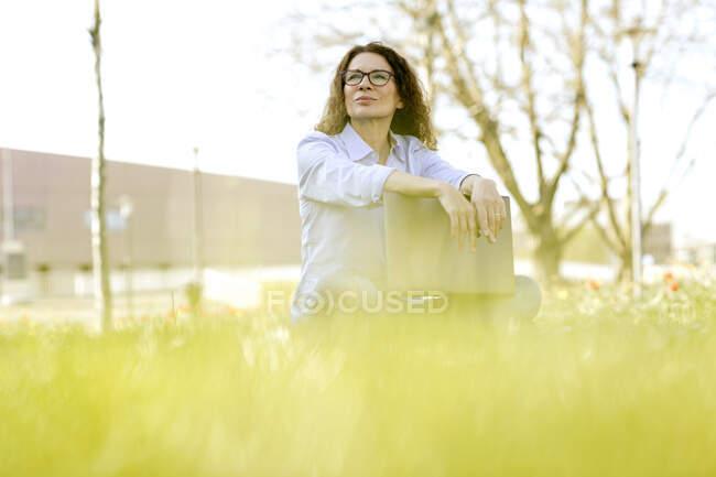 Портрет женщины с ноутбуком, сидящей на лугу и смотрящей на расстояние — стоковое фото