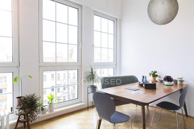 Обеденный стол в светлой гостиной с большими окнами — стоковое фото